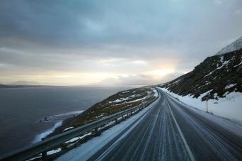 Route en bordure d'océan à la sorite de Siglufjordur, en islande à vélo en hiver